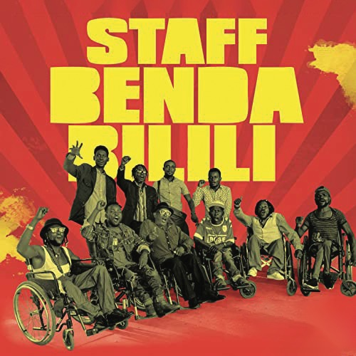 A photograph of Staff Benda Bilili posing in front of a red background with their band name in large yellow block letters