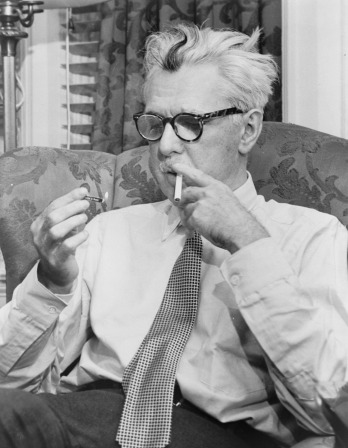 black and white photo of James Thurber lighting a cigarette in the new york times office