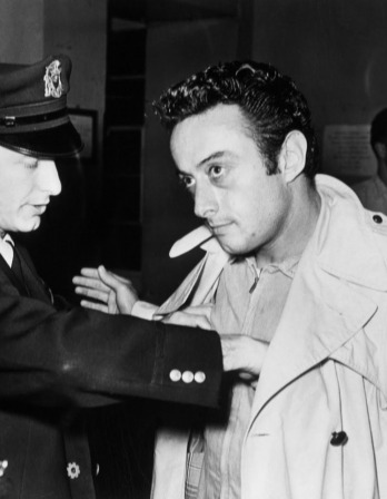 Black and white photo of Lenny Bruce being frisked by an officer