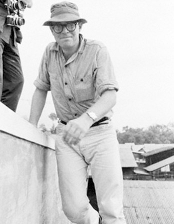 Black and white of photograph of American writer Michael Herr standing.