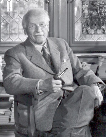 Black and white photograph of Swiss psychiatrist Carl Jung seated with legs crossed.