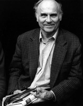 Black and white photograph of Ryszard Kapuściński holding a book.