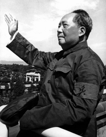 Black and white photograph of Mao Zedong with raised arm.