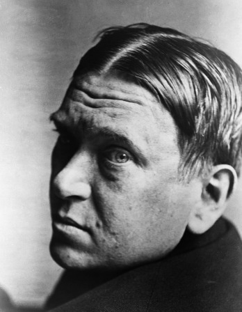 Black and white photograph of Mencken looking over his shoulder at the camera