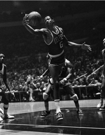 Bill Russell leaps for a basketball while playing for the Celtics.