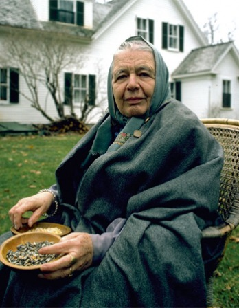 Photograph of Marguerite Yourcenar with a headscarf sitting in a chair outside.