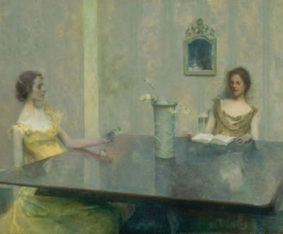 Two women wearing formal dresses sit at a large table, one reads a book. There is a vase of flowers at the center of the table.