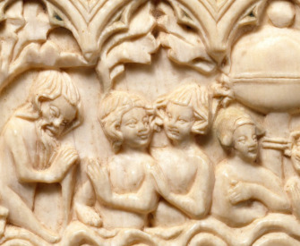 A medieval ivory carving depicting an old man entering the fountain of youth, which already contains two young couples.