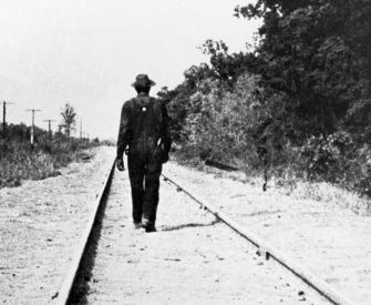 Hobo walking along railroad tracks, United States, c. 1930. Photographer unknown. © Private Collection / Peter Newark Pictures / Bridgeman Images.