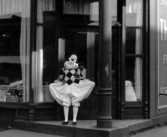 Black and white photograph of a clown laughing in front of a storefront.