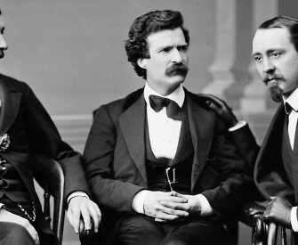 Black and white photograph of Mark Twain sitting between two men.