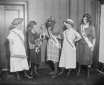 """Photograph of Margaret Gorman presenting the wooden cup to the winner of the Advertising Club's """"beauty"""" contest, 1921."""