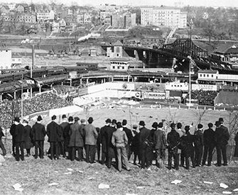 Baseball fans stand on Coogan's Bluff to watch the New York Giants play the Chicago Cubs, Polo Grounds, New York City, September 23, 1908.