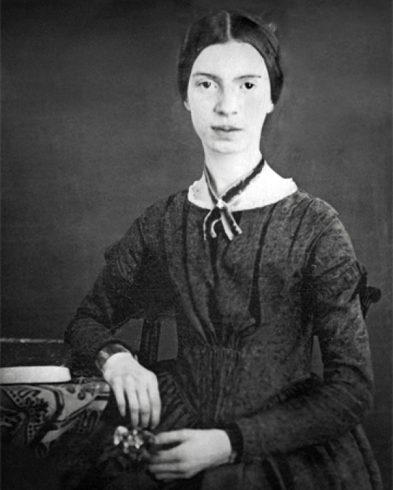 Black and white photograph of Emily Dickinson sitting next to a desk.