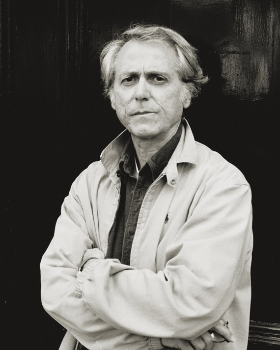 Don Delillo standing outside in a jacket, black and white photo