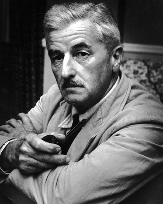 Photograph of William Faulkner sitting in a chair.
