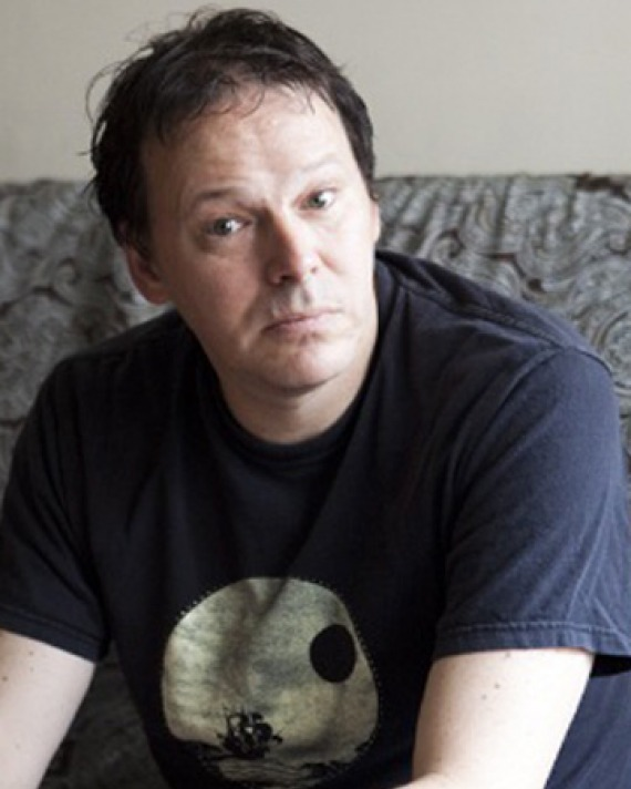 Color photograph of author David Graeber wearing a t-shirt.