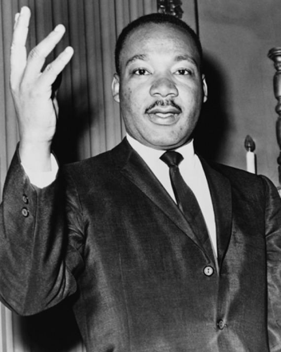 Black-and-white photograph of Martin Luther King Jr. with his right hand lifted