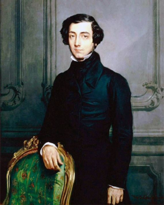 Portrait of Alexis de Tocqueville wearing a black suit and standing in front of a chair.