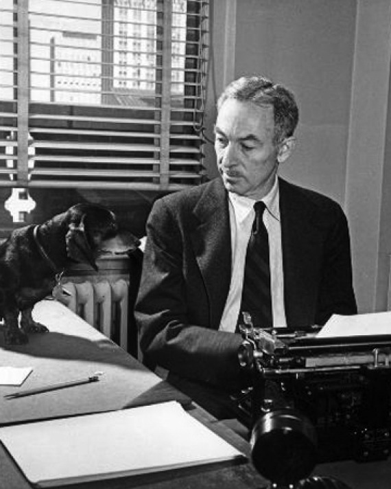 Black and white photograph of E. B. White sitting at his typewriter with his dachshund.