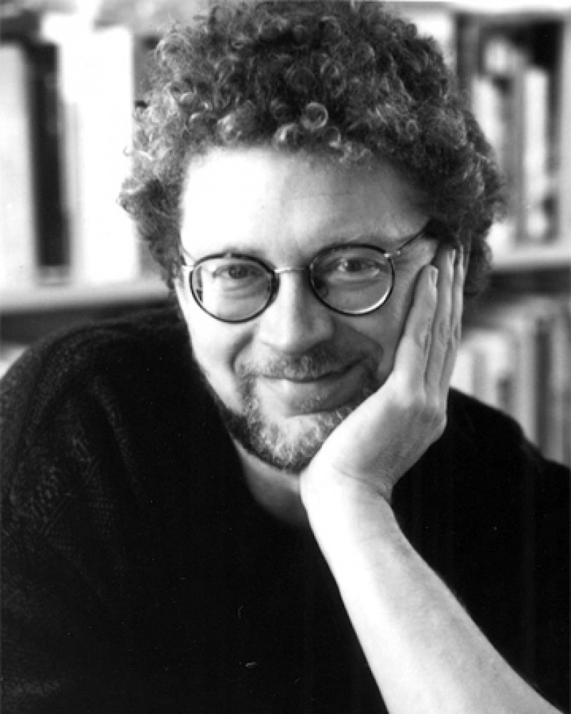 Black and white photograph of Sven Birkerts sitting in front of a bookshelf.