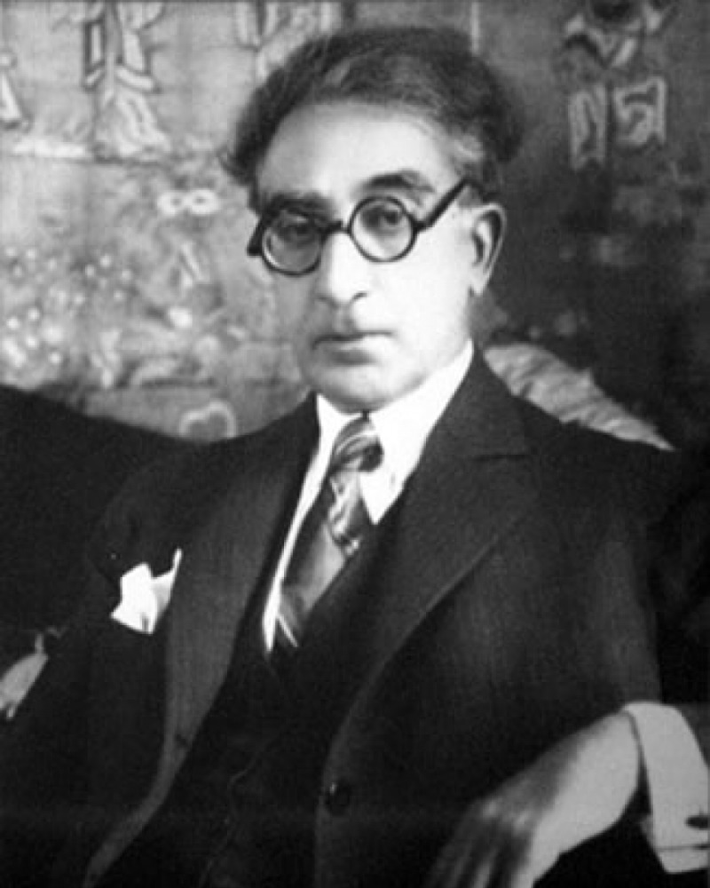 Black and white photograph of C. P. Cavafy wearing thick-rimmed black glasses.