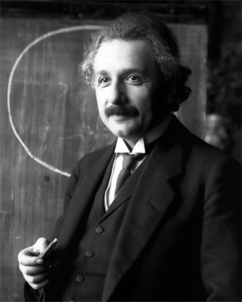 Albert Einstein in a suit and tie standing in front of a chalkboard