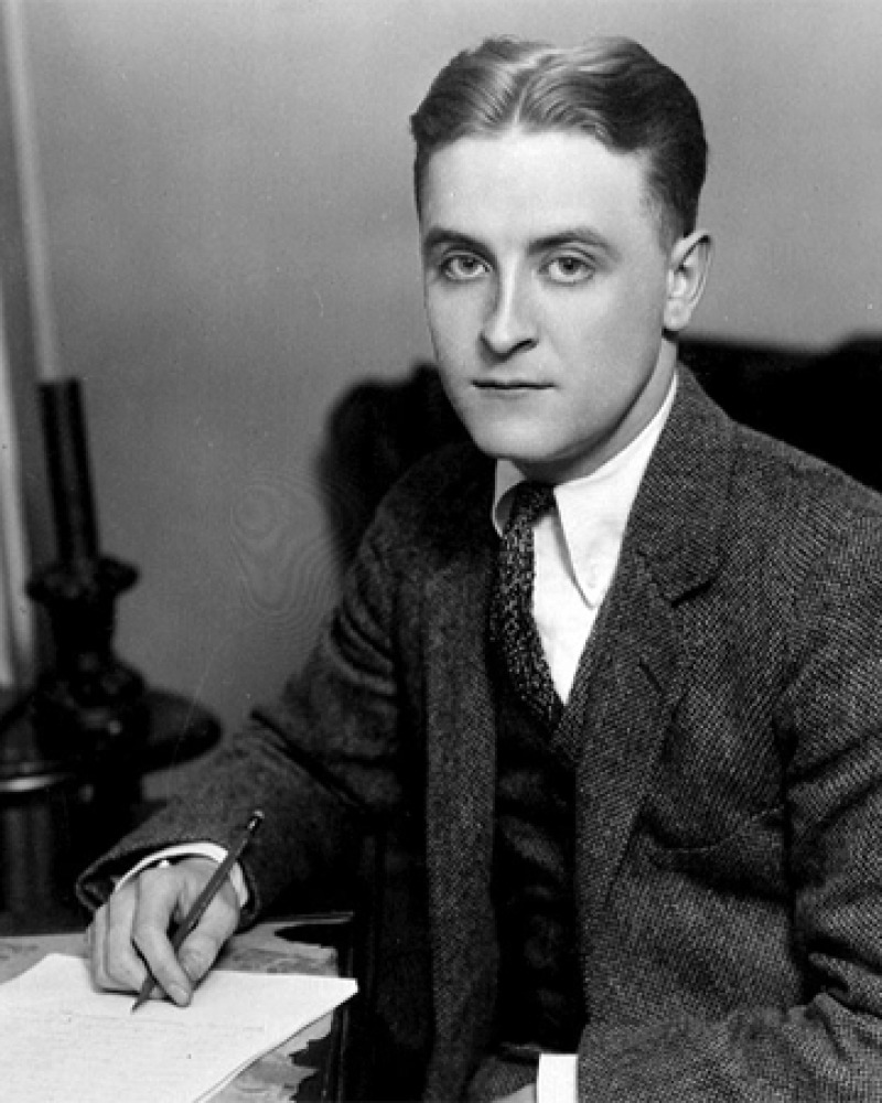 Black and white photograph of a young F. Scott Fitzgerald sitting at a desk.