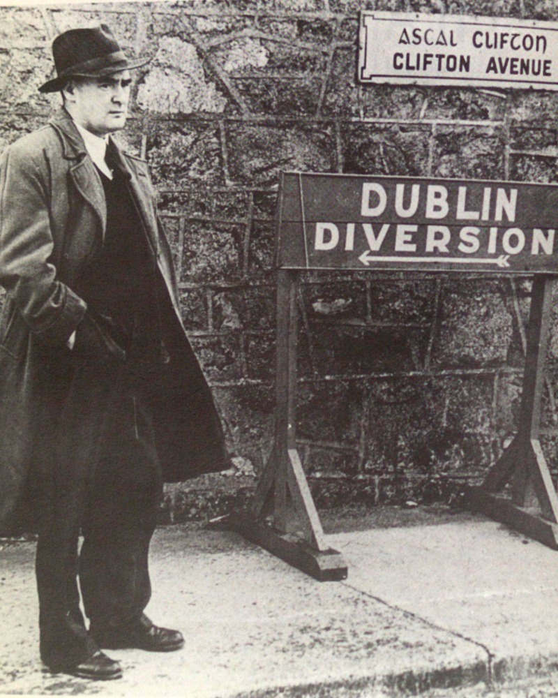 Flann O'Brien in an overcoat standing next to a Dublin Diversion sign