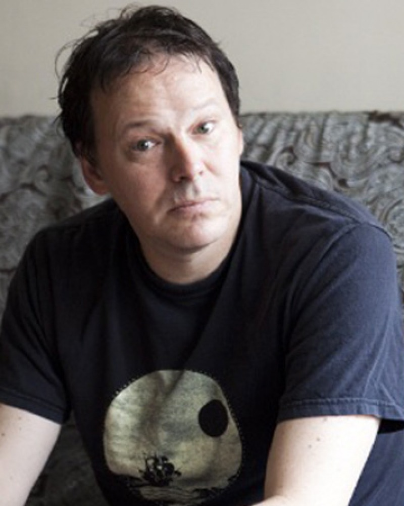 Color photograph of author David Graeber wearing a t-shirt.