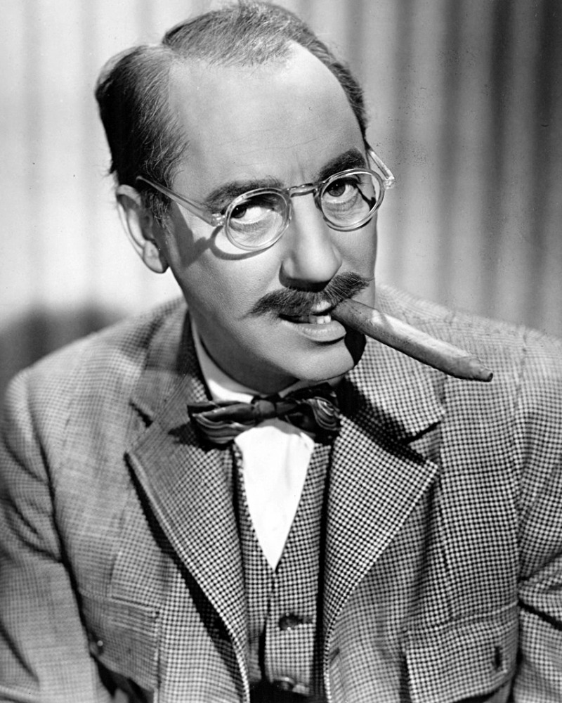 black and white photo of Groucho Marx wearing glasses and smoking a cigar from the side of his mouth