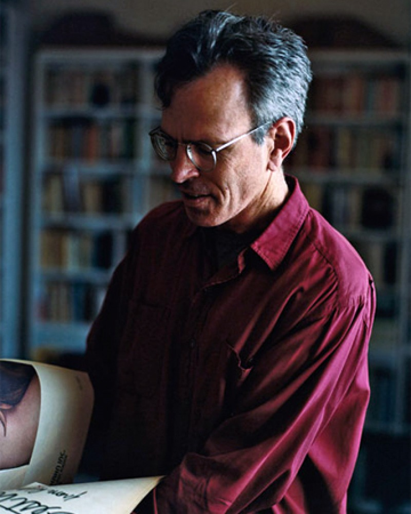 Photograph of Jim Holt looking at a book.