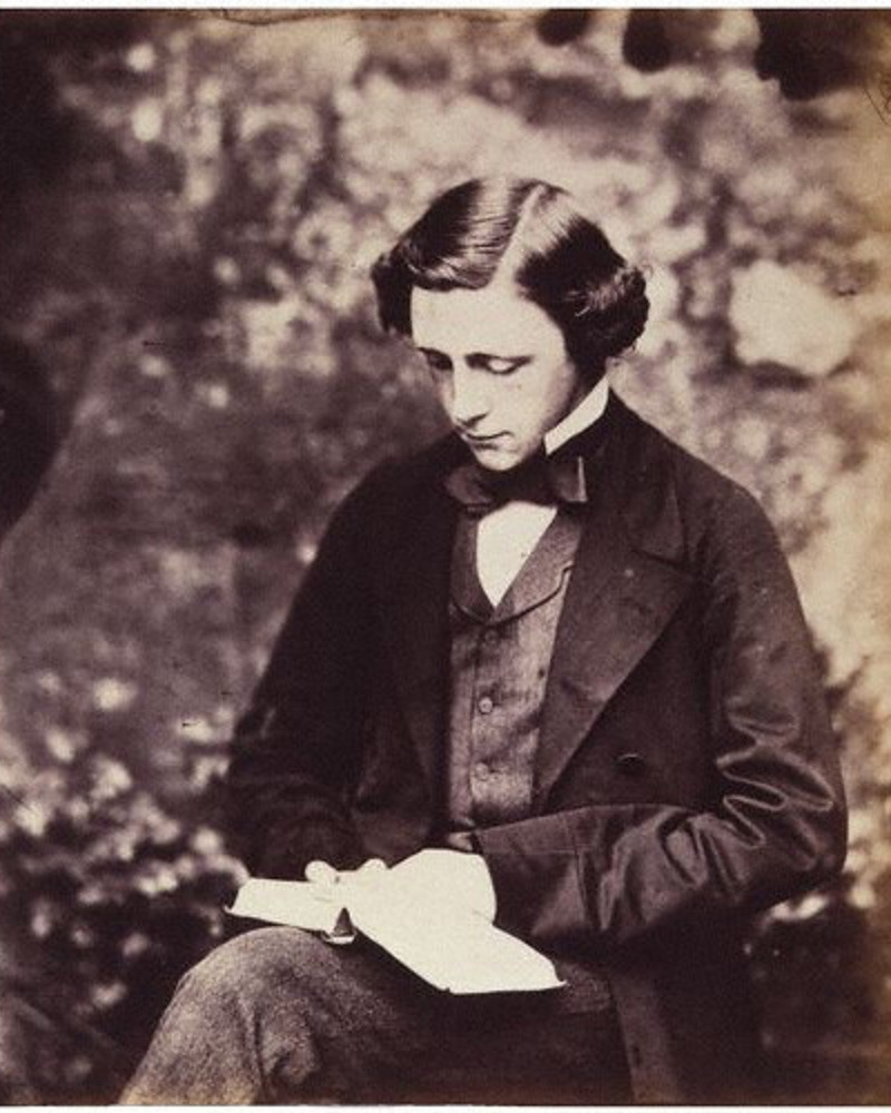 Sepia toned photograph of Lewis Carroll in a suit, reading a book