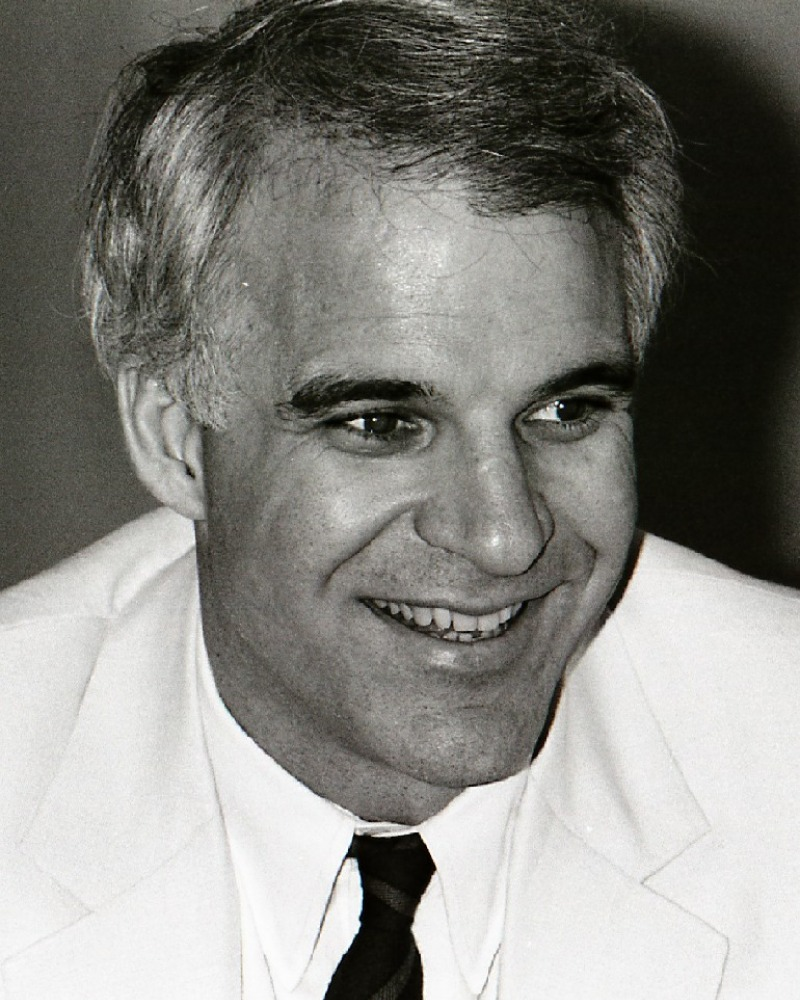black and white photo of Steve Martin wearing a white dinner jacket and black tie