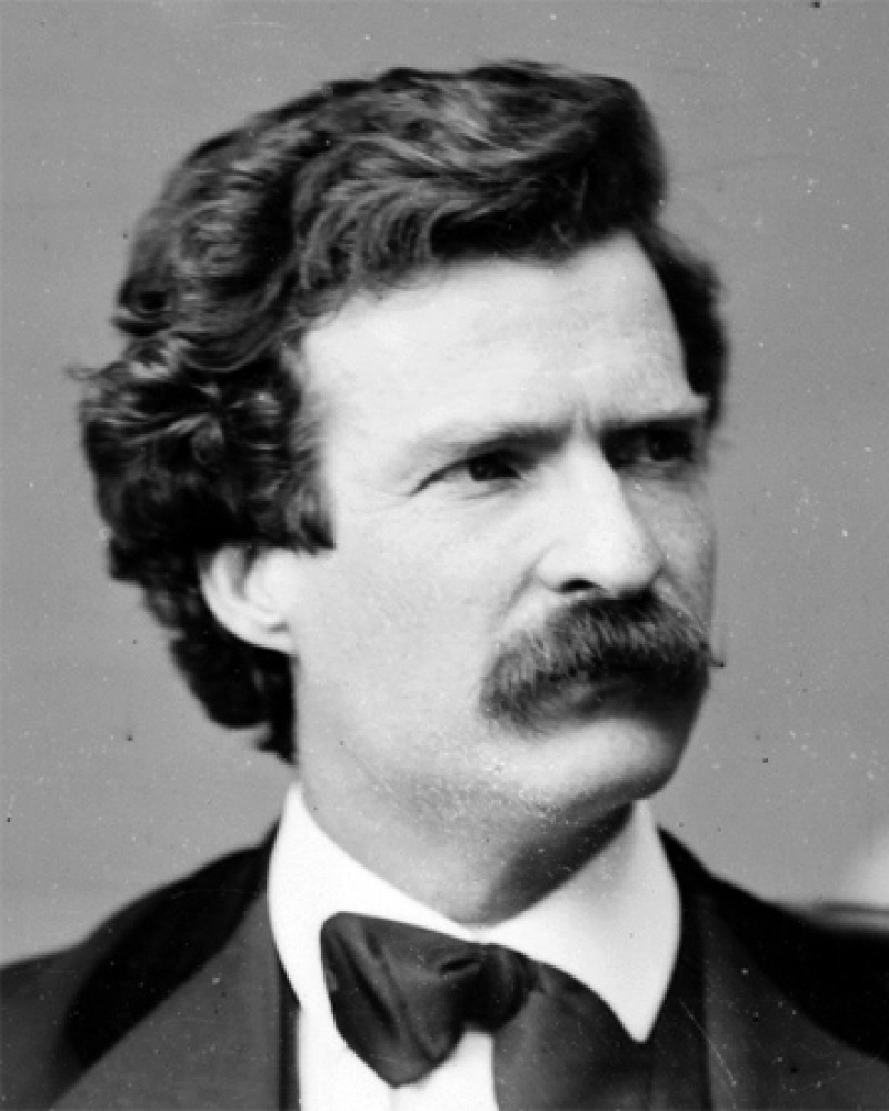 Black and white photograph of a young Mark Twain with dark hair.
