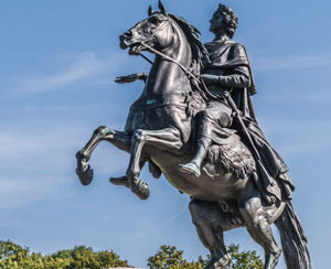 A bronze monument of a man on a horse.